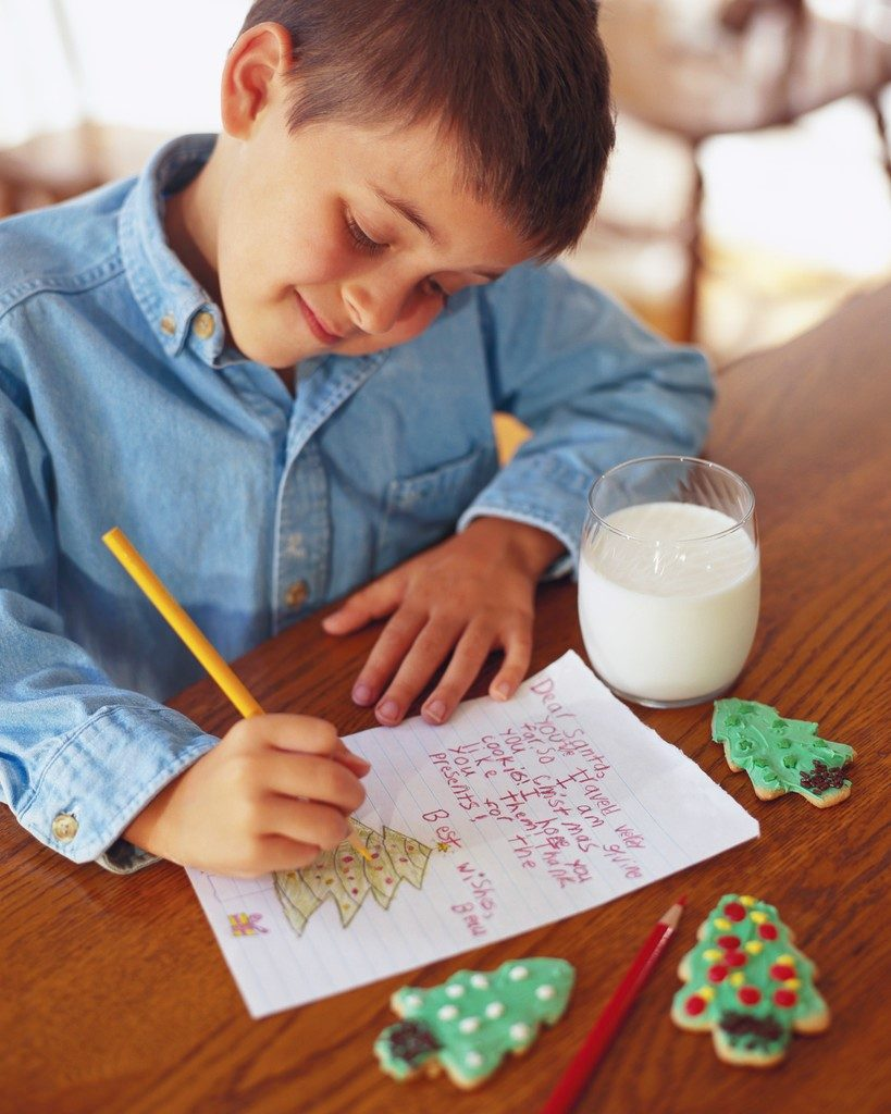 Boy writing a Christmas letter to Santa