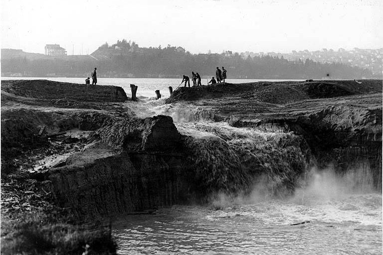 Cutting away the cofferdam at the Montlake Cut between Lake Washington and Lake Union. December 1913. Photographer unknown.