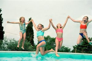 girls jumping into swimming pool