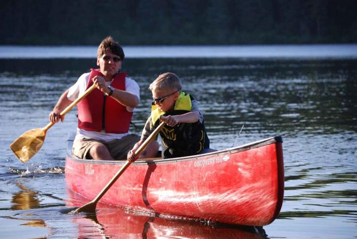father and sone canoeing on a river