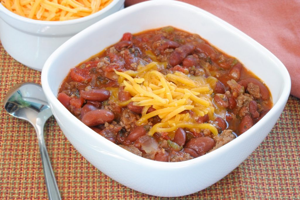 Homemade chili with beef and beans, garnished with shredded cheddar cheese