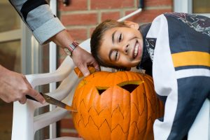 Mother and son carving jack-o-lantern pumpkin