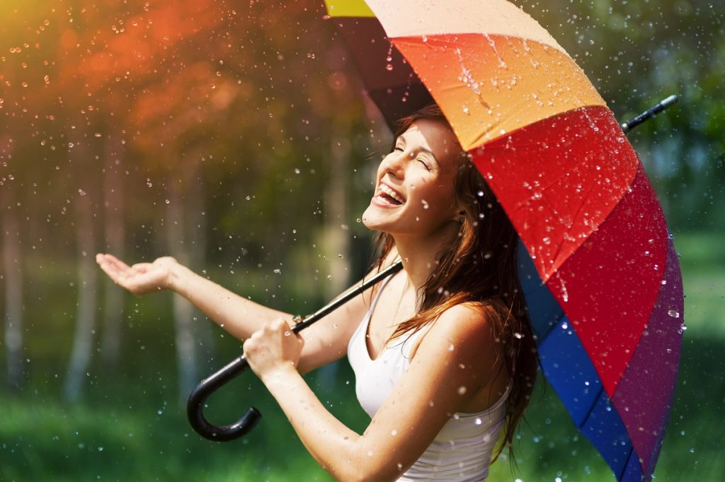 Laughing woman with umbrella checking for rain