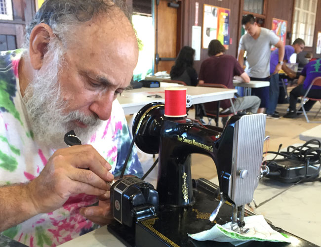 man repairing sewing machine