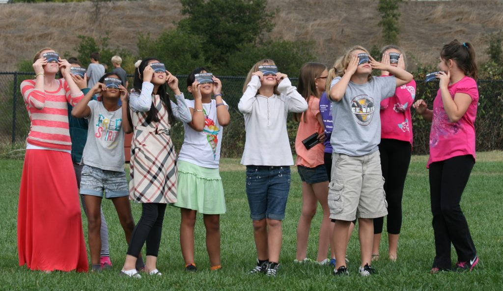 Girls using eclipse viewing shades photo by Mark Margolis, Rainbow Symphony