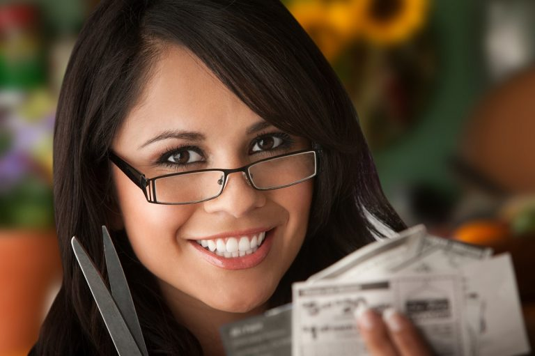 Woman saves money by clipping coupons photo by creatista - DepostiPhotos.com