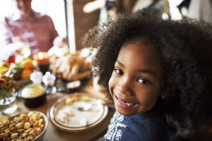 Happy young girl at Thanksgiving dinner