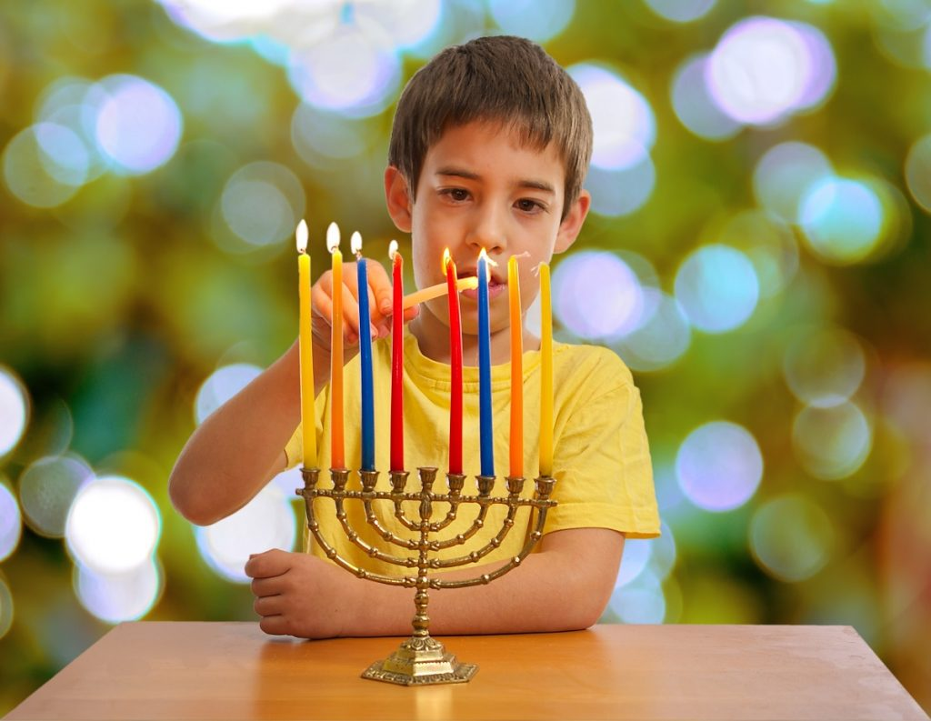 Jewish Boy lighting a Hanukkah Menorah