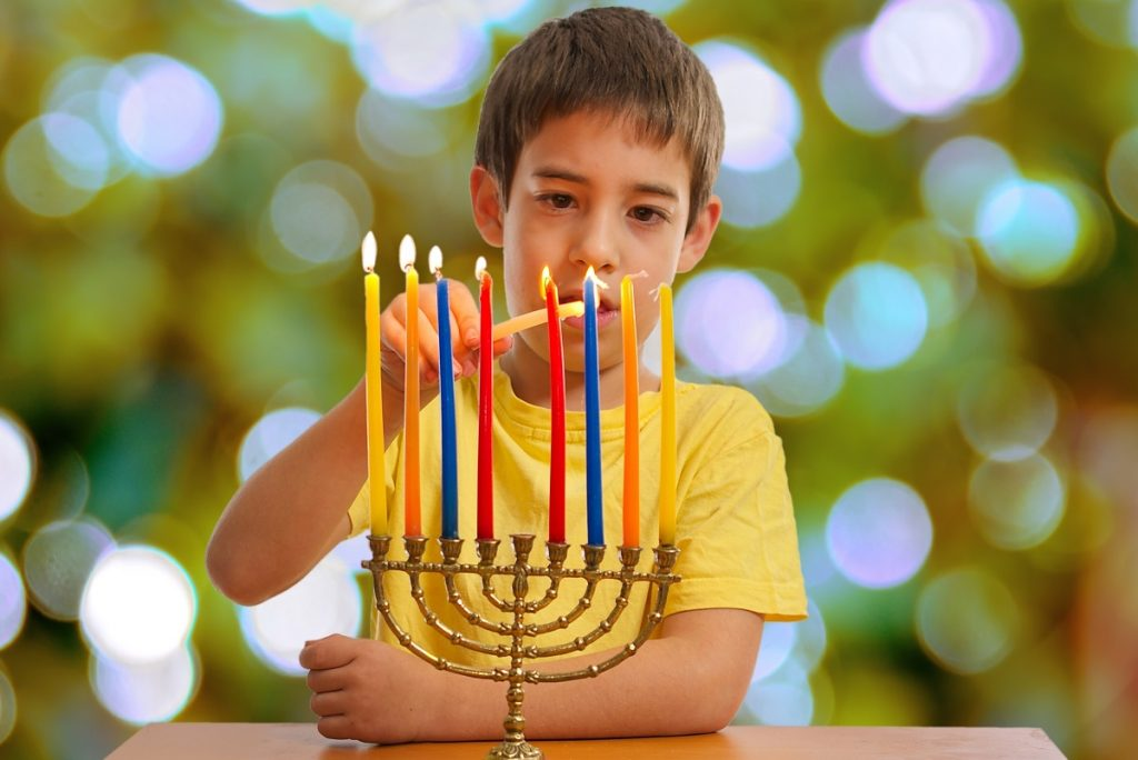 Jewish Boy lighting a Hanukkah Menorah
