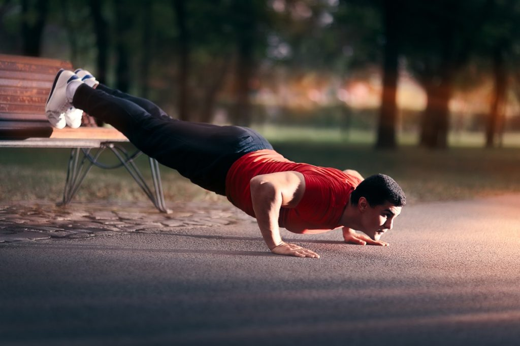 man doing calesthenics using a park bench