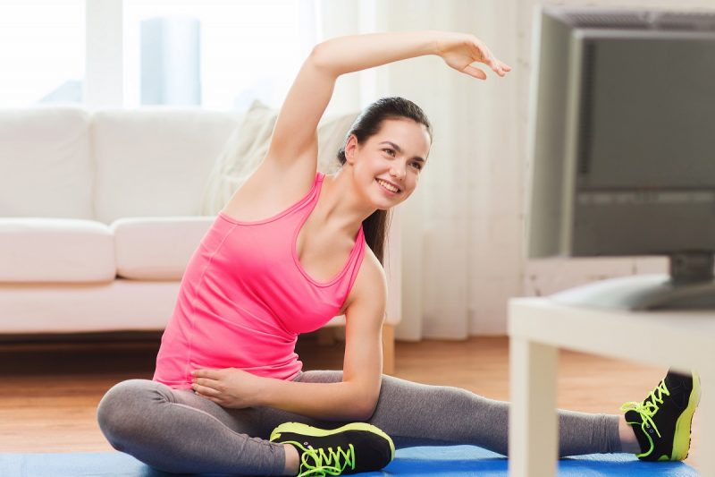 woman exercsing at home using a video - DepositPhotos.com