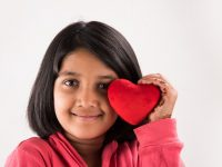 young girl with red valentine heart