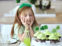 Young girl admiring St. Patrick's Day cupcakes