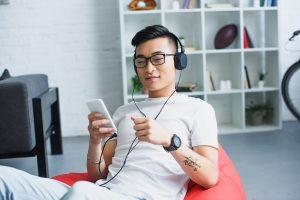 Young man listening with headphones. Photo by VitalikRadko - DepositPhotos.com