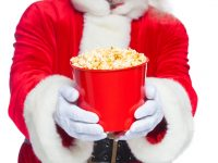 Santa Claus at the movies with bucket of poprcorn photo by satyrenko - Depositphotos.com