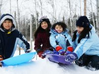 Family enjoying a snow day in the park - DepositPhotos.com