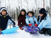 Family enjoying a snow day in the park - DepositPhotos.com