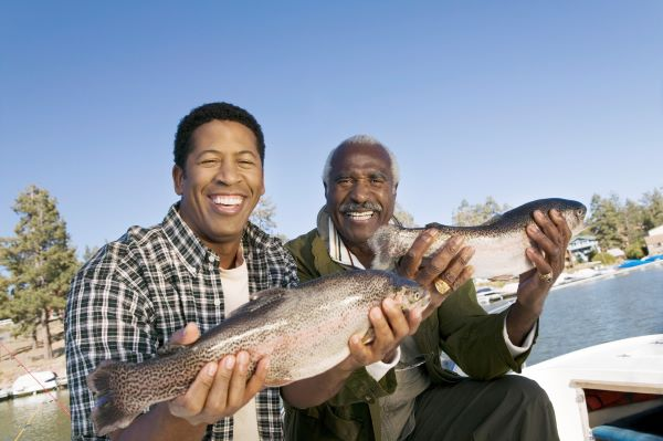 Father and son fishing, showing off their catch