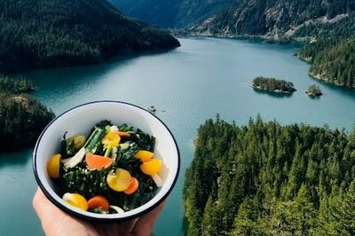 hiker holding a bowl of food with mountain lake in background