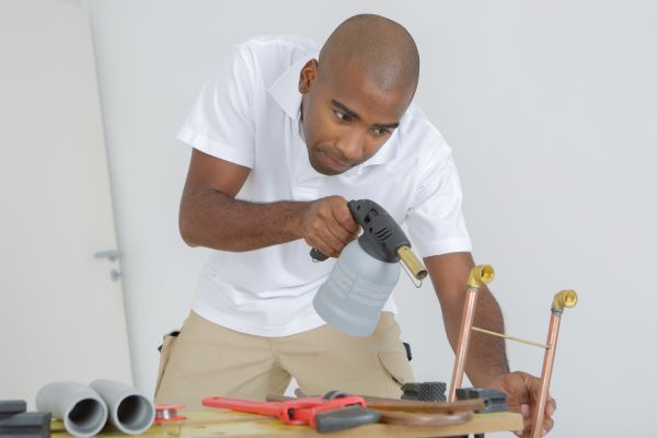 Man using tools to doing plumbing repairs, soldering a copper pipe