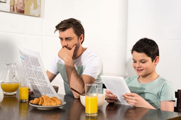 Father and son reading at breakfast