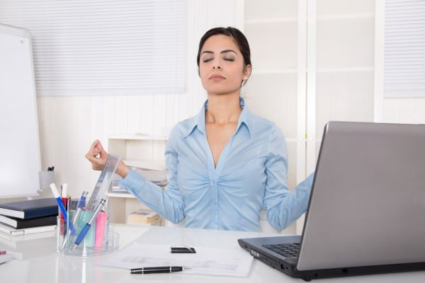 woman meditating at work at her desk