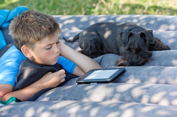 young boy reading an ebook outside with his dog