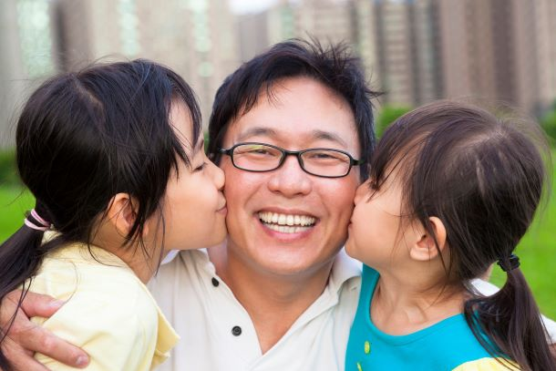 children kissing their father
