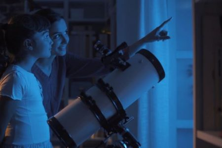 Mother and daughter stargazing with a telescope