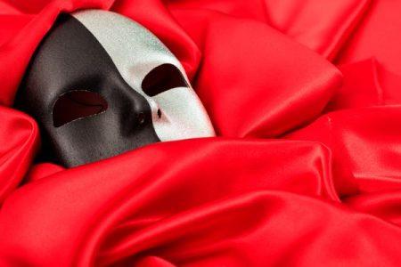 black & white carnival mask on red background