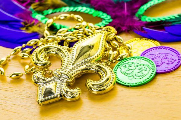 mardi gras trinkets (fleur de lis, coins, beads, mask)