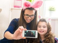 Mother and daughter wearing bunny ears taking a selfie photo