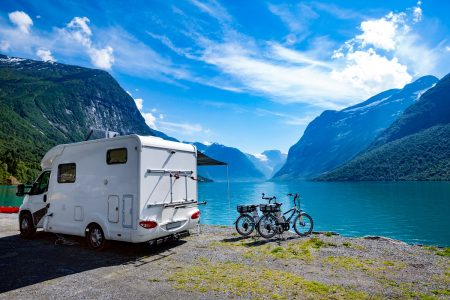 RV camper and bikes parked by a mountain lake