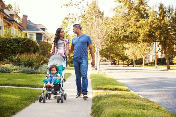 couple walking with child in stroller