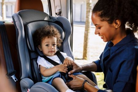 mom fastening child in car seat