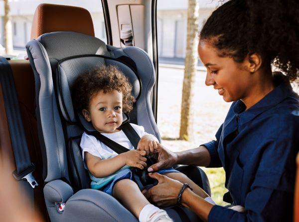 mom fastening child in car seat